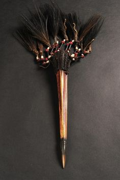 Papua New Guinea, Asmat  presumably cassowary bone, split and sharpened, horn tip, fixed with blackish mass, swivel head coated with plaited cord, strings with abrus beans, coix seeds and cassowary feathers affixed
