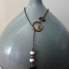 """Collier cravate, type sautoir de  65 cm, avec un pendentif oiseau"""", agrémenté de 4 perles de culture véritable et d'un noeud"""