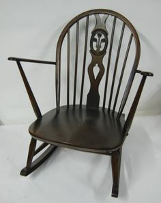 A wonderful 1960s Ercol Rocking Chair in great condition. In Dark Elm with a 3 feather design to the rear.