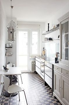 Grey galley kitchen. Really loving the hutch-style cabinets with glass. Lovely.