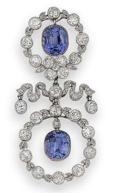 A belle époque sapphire and diamond brooch, circa 1905 In the Garland Style, composed of two old brilliant and rose-cut diamond wreaths with millegrain detail, each surrounding a cushion-shaped sapphire drop, connected by a rose-cut diamond fluttering ribbon with oval-cut diamond terminals, diamonds approximately 5.60 carats total, signed Cartier Paris to the edge of the sapphire collet.
