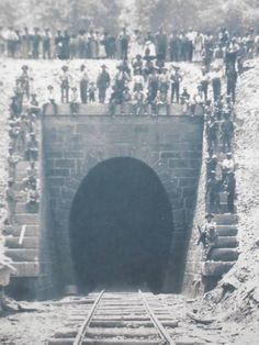 Old photo of the Dingess Tunnel. You can see the tracks leading into it and many people standing around the opening.