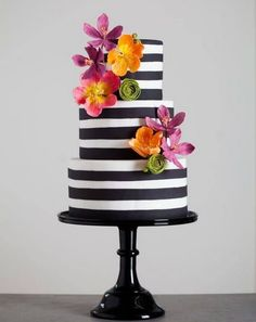 Black and white striped cake with tropical flower detail.     ᘡղbᘠ