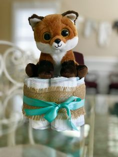 A centerpiece I did for my daughters Woodland baby shower. 6 diapers and a stuffed animal. Easy yet really cute.