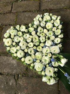 Trauerherz mit weißen Ranunkeln und blauen Traubenhyazinthen