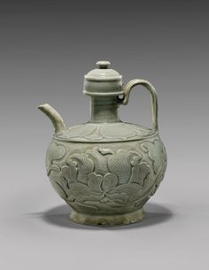 Rare Chinese early Yaozhou celadon glazed ewer: of globular form set on a slightly splayed foot, with a thick strap handle, and with a short curved spout; the body showing deeply and sharply carved continuous design of peony blossom and foliage; and a slightly domed cover; Song Dynasty or earlier; H: 8""
