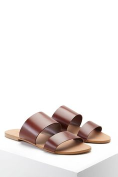 c0015b32f2d9 A pair of genuine leather slides featuring dual straps across the front and  an open toe.