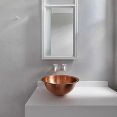 A simple copper basin provides the main embellishment in this white and grey bathroom, which is located inside a Victorian flat in London.