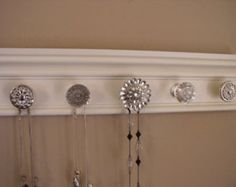 Jewelry organizer  wall rack hung necklace hanger features a rhinestone center  & 5 knobs total on off  white finished 15 inches long