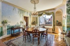 This Upper East Side co-op has wood tile flooring, a circular dining table, beautiful wrap-around mural, wooden bar-cart, semi-circular inlets for statues, green drapes and a hanging chandelier.