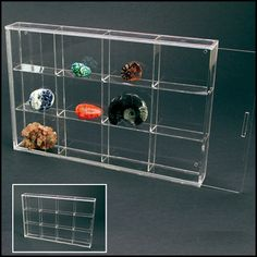"""Made of crystal clear acrylic glass, these sleek cabinets are made to hang on your wall and come in 6 different styles/sizes.  Since they are frameless and hingeless, the focus is on your collection, not the hardware.  The clear front panel slides into place.  Hang over a mirror and add top UV lighting for a dramatic effect to complement any decor. 12 compartments 2-3/4"""" x 2-1/2"""" x 11/16"""" each Overall cabinet size 11-13/16"""" x 7-7/8"""" x 13/16"""" deep"""