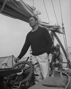 Actor Errol Flynn with his dog at the helm of a yacht while enjoying a fishing vacation, circa 1941.