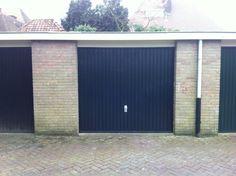 Stalen kiep kanteldeur, rijp om vervangen te worden door een geïsoleerde sectionaal deur