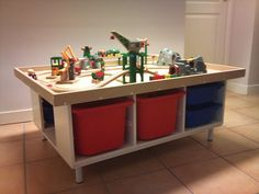 Build your own play-table from IKEA pieces.  To dampen the sound, glue a fabric on the table top.