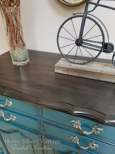 "I am in love with this color! It's a beautiful deep peacock called ""feathered nest"" by Heirloom Traditions Paint. I distressed the edges and black glazed to keep that vintage look and kept the original hardware. The top could not be restained due to the many years of wear/imperfections so I did the next best thing and painted it to look like wood! :)"