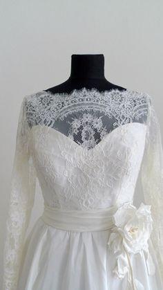 Svatební šaty s rukávem Vypasované šaty z jemné krajky a krásného taftu ve smetanové barvě. Bavlněná krajka s bordurou a medailony.  Dlouhý úzký rukáv, skrytý zip na zadním dílu. Celé šaty jsou podšity dyšesem a vypodšívkovány. Velikost 36-38 /obvod přes prsa 82cm/, mohu ušít i v bílé a v jiné velikosti. Doplněno květinou ze stejné látky od firmy Moraviaflor.