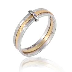 Stacked Gold Bands | An exquisite wedding band, featuring three rough and earthy looking rings with polished finish carefully stacked and held together with a gold clip resembling a twisted rope. The middle band is yellow gold and is centred between two white gold bands. The ring is perfect imperfection, trendy and stylish and for someone looking for something a little less classic. A gorgeous unisex ring. By Neta Wolpe #stackedbands #unisexring #twotonesrings #stackingrings…