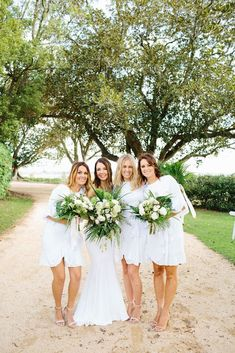 Bridesmaids in white mismatched cocktail dresses with green and white bouquets for modern romantic wedding | Tim Coulson