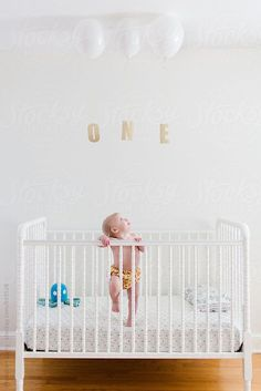 Cute baby standing in a crib on her first birthday with balloons and the word one by meaghancurry   Stocksy United