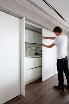 It makes so much sense when space is tight: kitchens concealed behind accordion doors, sliding doors, cabinet doors—anything it takes to keep the clutter out of sight.