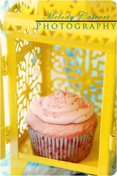 Pink cupcakes in a yellow metal lantern with a vintage fabric background.