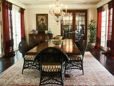 Casual dining is emphasized by the use of wicker chairs in combination with the overall formality of the architecture. The drapes are custom-dyed tulle with hand appliqued velvet.