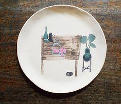 歲月靜好。白陶盤中畫有一張木桌,桌上擺有一些瓶罐杯具,桌下伏卷著一隻黑貓,呈現薛慧瑩所嚮往的美好生活