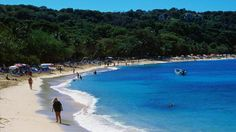 7 Reasons to Love Puerto Plata | Tourists stroll along the shore next to blue waters lapping the sand at Sosua beach.