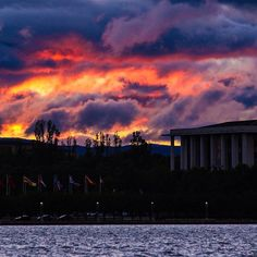 An incredible Canberra sunset creates a dramatic backdrop to the International Flag Display and the National Library of Australia! #visitcanberra #seeaustralia Photo: Photographer and Instagrammer wanderlust73