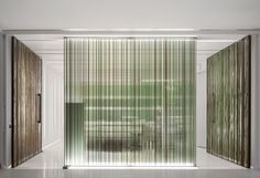 Stripy glass screens obscure views between rooms at a dental clinic - Patterned with vertical stripes of green and black, the semi-transparent walls surround the reception and waiting area of the clinic and are made from recycled glass panels of different thicknesses - Dental clinic in Torres Vedras, Portugal, by MMVArquitecto