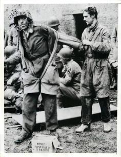 1944- German parachute trooper, captured by U.S. forces in fighting near St. Lo, France, is helped out of his uniform by a German medical corpsman at an American forward dressing station.