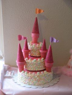 """Used cake and sugar cones (coated in corn syrup, rolled in pink sugar) with colored marshmallows (sliced in half) to create the """"bricks"""" of the castle.  My first attempt at stacking…"""