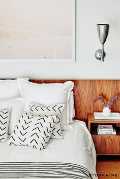 Midcentury modern bedroom with wood backsplash, a wooden bedside table, a silver sconce, and white bedding with printed throw pillows