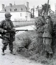 Turqueville, june 7, 1944. Many 101st troopers were dropped far from their initial DZ's. Like Wilbur W. Shanklin, holding his M-1, with fixed bayonet on a rather terrified German officer (identifiable as such by his belt). Shanklin belonged to RHQ/506th PIR and the German was quite likely a member of the 795th Ost Battalion. They are on the road between Sainte-Mère-Eglise and Audouville-la-Hubert.