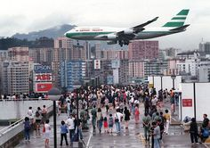 Hundreds of Hong Kong people gather onto Kai Tak Airport's rooftop carpark 27 June to capture a momento of planes making their approach toward the...
