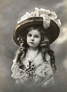 Vintage tinted portrait of late Victorian-Edwardian era girl with a huge hat and big ringlets. Beautiful