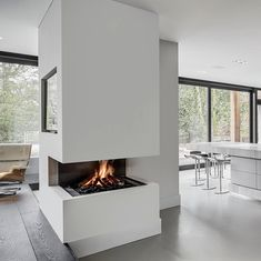The dark steel backdrop and warm, dancing flame in our 3-sided fireplace presents a striking contrast to the white kitchen and lounge spaces it separates. Raised from the floor at seated eye level, it can be enjoyed throughout, visible from every corner of the room. 3 Sided Fireplace, Open Fireplace, Fireplace Wall, Living Room With Fireplace, Wall Fireplaces, Fireplace Ideas, Living Room Modern, Living Room Designs, Living Room Decor