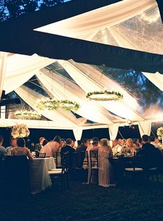 Fabric draped over a clear tent adds another dimension, and those  greenery chandeliers!