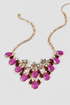 "Add a touch of elegance to your outfit with the Lisbon Statement Necklace.  This gorgeous necklace combines fuchsia and deep red teardrop stones with iridescent rhinestones to create a one of a kind accessory.  Pair this with a dress and heels for a great night time look.<br /> <br /> - Finished with a lobster claw clasp<br /> - 20"" length<br /> - 3.5"" extension<br /> - Lead & nickel free<br /> - Imported"
