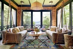 Chairs and stools from Noho Modern flank a cocktail table by Mecox on the master wing's sleeping porch; Thom Filicia designed the slate-color throw for Eastern Accents and the carpet for Safavieh.