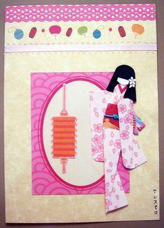 "Materials: Cardstock with border print; decotape; ribbon; frame and lantern from mylittleshoebox's ""Aiko"" scrapbook set; kimono (yuzen washi); obi (origami paper); viscose string on obi; flower on hair (nail sticker).  Dimensions: Card (12 cm x 17.2 cm); doll (11.5 cm tall)."