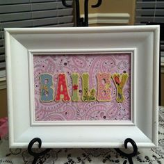Made for a baby shower decoration. Small wood letters and scrapbook paper placed in a frame and set on a plate stand. http://bit.ly/HN4251
