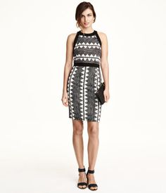 Knee-length, sleeveless, fitted dress in jersey with decorative stitching. Seam at waist and visible back zip.