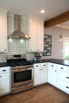 Fixer Upper hosts Chip and Joanna Gaines renovated the homeowners' kitchen and added a new stainless steel range and vent hood surrounded by a beveled subway tile backsplash. Crisp white cabinetry and black marble countertops complete the stylish look. Black Marble Countertops, Stainless Backsplash, Kitchen Countertops, Kitchen Backsplash, Backsplash Ideas, Black Backsplash, Stone Countertops, Subway Backsplash, Stainless Kitchen