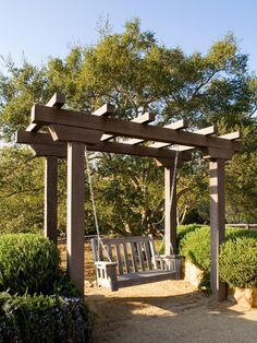 A lovely wooden arbor with attached swing is bordered by ornamental shrubs in raised garden beds.