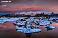 Jökulsárlón glacier lagoon in the twilight | Where to go in Iceland: Titanic icebergs float magnificently on Jökulsárlón, a majestic sky-blue glacier lagoon, where travellers can sail among the countless mountains of ice that constantly fall from the glacier.