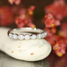 This vintage inspired half eternity band features dazzling conflict free diamonds set in solid 14k white gold pear and round shaped bezel setting
