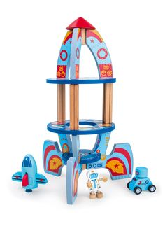 Die bunt bemalte Rakete aus Holz bietet der kleinen Astronautenfigur einen perfekten Start- und Landeplatz für sein Spaceshuttle. Begleitet wird er von einem Roboter auf Rädern – Ob Weltraum Hündin Leika vielleicht auch mitfliegen darf?  ca. 21 x 21 x 36 cm