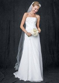 This chiffon over satin wedding dress showcases its beauty in all the right places for the ultimate glamorous effect! Strapless chiffon over satin gown features magnificent beaded lace appliques. Side draped skirt adds dimension and helps create movement. Sweep train. Sizes 0-14.