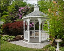 8 Vinyl Octagon Gazebo shown with Gray Composite Deck, 2x2 Decorative Spindle Rails, Decorative Posts, Cupola, Vinyl Finished Ceiling, Wavy Fascia, Old English Pewter Asphalt Shingles, and Hidden Wiring w/ 1 Receptacle & Switch.